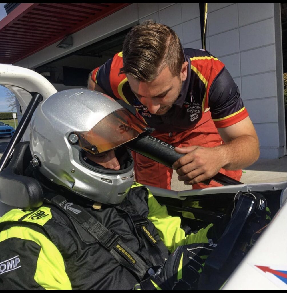 Jonathan Scarallo instructing a racing driver trackside